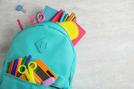 Stylish backpack with different school stationary on white table, top view. Space for text