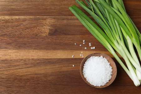 Fresh green onions and bowl of salt on wooden background, top view. Space for text