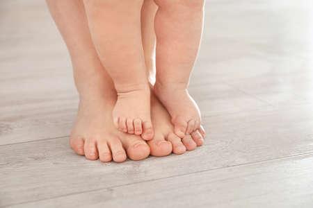 Madre e il suo bambino in piedi sul pavimento, primo piano delle gambe