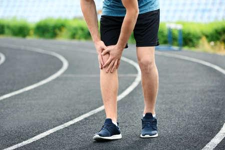 Man in sportswear suffering from knee pain at stadium, closeup