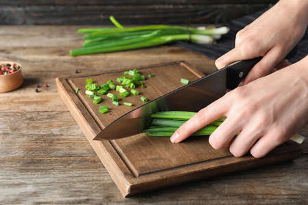 Woman cutting fresh green onion on wooden board at table, closeup