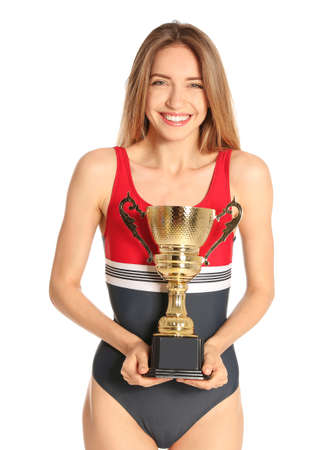 Happy young woman in swimwear holding golden cup on white background