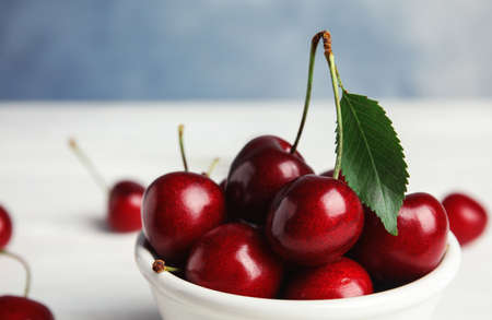 Bowl with sweet cherries on white table, closeup