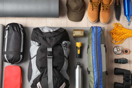 Flat lay composition with different camping equipment on wooden background