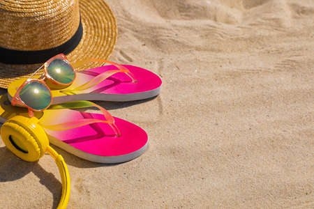 Different beach accessories on sand, space for text. Summer vacation