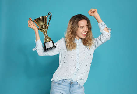 Portrait of happy young woman with gold trophy cup on blue background