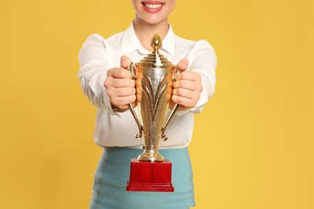 Jonge onderneemster met gouden trofeekop op gele achtergrond, close-up Stockfoto