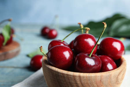 Wooden bowl with ripe sweet cherries on table, closeup. Space for text