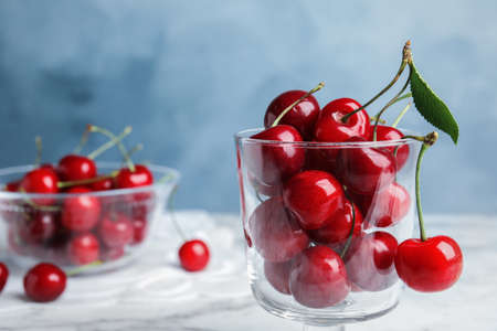 Glass dessert bowl with ripe sweet cherries on marble table. Space for text