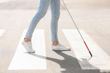 Blinde persoon met lange stok die de weg oversteekt, close-up Stockfoto