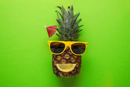 Faccia buffa fatta di ananas, occhiali da sole e fetta di agrumi con ombrello da cocktail su sfondo colorato, vista dall'alto
