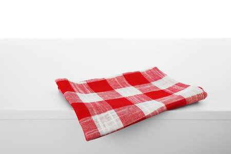 Folded kitchen towel on light table against white background