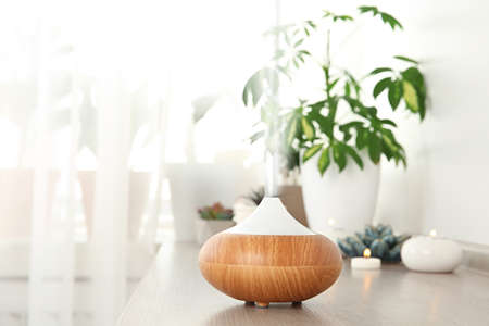 Composition with modern essential oil diffuser on wooden shelf indoors, space for text