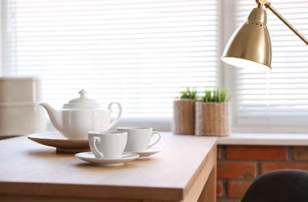 Juego de té en la mesa junto a la ventana con persianas en el interior