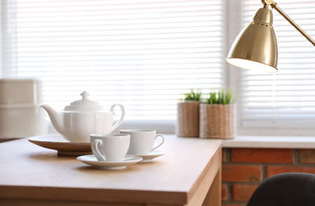 Tea set on table near window with blinds indoors