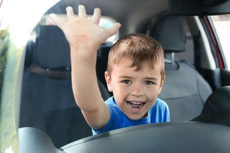 Schreiender kleiner Junge geschlossen im Auto. Kind in Gefahr