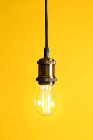 Hanging modern lamp bulb against yellow background Imagens