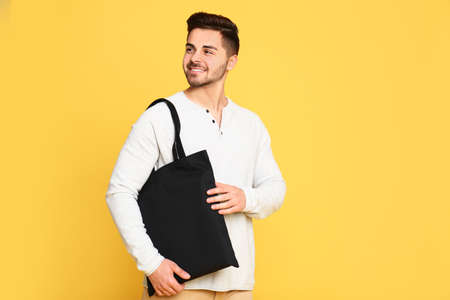 Portrait of young man with eco bag on yellow background. Space for text 写真素材