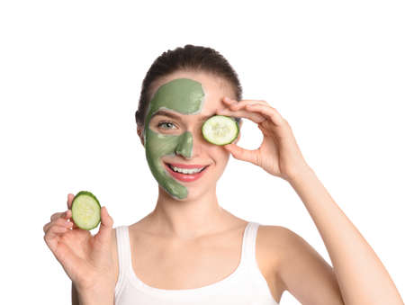 Young woman with clay mask on her face holding cucumber slices against white background. Skin care