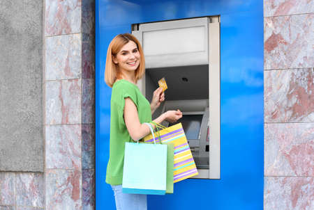 Beautiful woman with credit card near cash machine outdoors