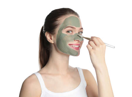 Young woman applying clay mask on her face against white background. Skin care