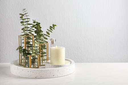Stylish tender composition with burning candle and plants on white wooden table against light background, space for text. Cozy interior element