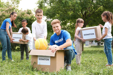 Volunteers and kids with donation boxes in park