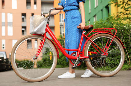Young woman with bicycle in city, closeup Imagens
