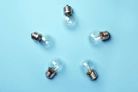 New incandescent lamp bulbs on light blue background, top view