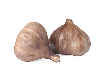 Unpeeled bulbs of black garlic on white background