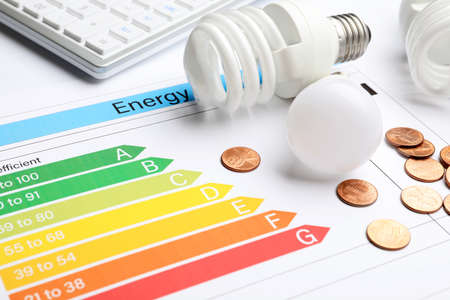 Energy efficiency rating chart, coins and light bulbs, closeup