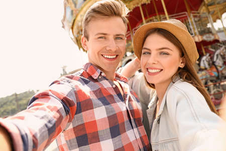 Young happy couple taking selfie near carousel in amusement park