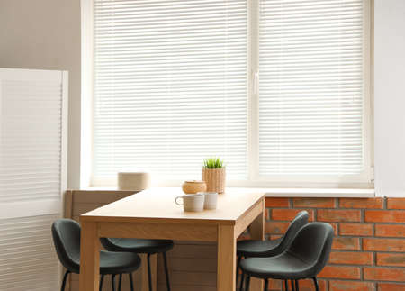 Stylish dining room interior with modern table set and window blinds