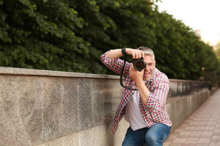 Handsome mature man taking photo with professional camera outdoors. Space for text