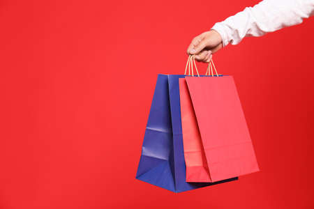 Young man with paper bags on red background, closeup. Space for text Stockfoto