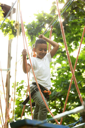 Little African-American boy climbing in adventure park. Summer camp