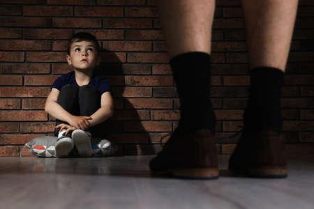 Hombre adulto sin pantalones de pie delante de un niño desesperado en el interior. Niño en peligro Foto de archivo
