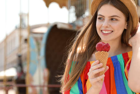 Young happy woman with ice cream cone in amusement park. Space for text