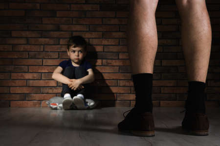 Adult man without pants standing in front of despaired little boy indoors. Child in danger