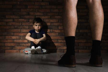 Hombre adulto sin pantalones de pie delante de un niño desesperado en el interior. Niño en peligro