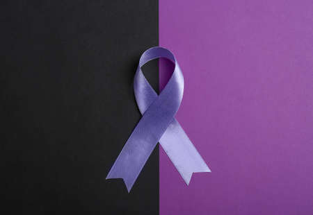 Purple awareness ribbon on color background, top view