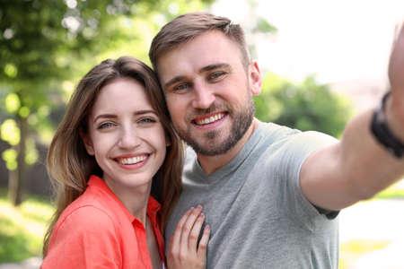 Feliz pareja joven tomando selfie en el parque