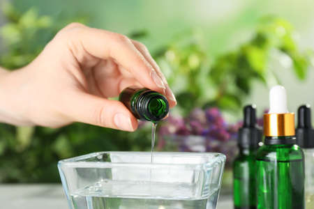Woman dripping essential oil into bowl on table, closeup Stock Photo