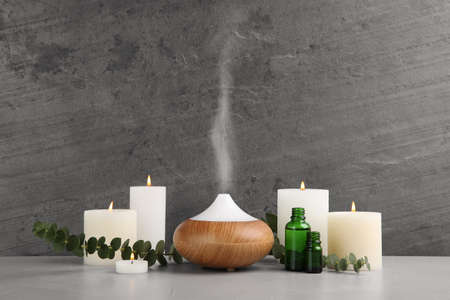 Composition with essential oils diffuser on table against grey background. Space for text