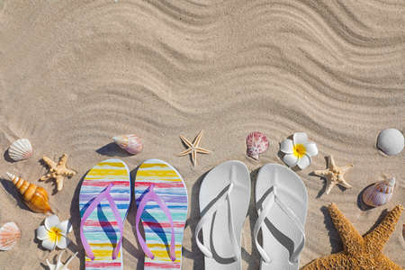 Flat lay composition with flip flops and space for text on sand. Summer beach accessories