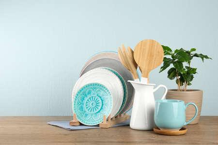 Planta en maceta y juego de utensilios de cocina en la mesa de madera cerca de la pared clara, espacio para texto. Diseño de interiores moderno