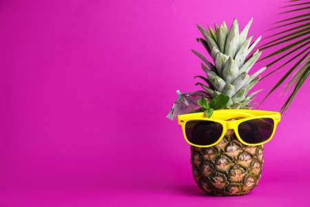 Fresh pineapple with sunglasses, umbrella and mint as summer cocktail on color background, space for text
