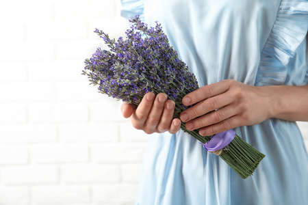 Woman holding fresh lavender flowers against white brick wall, closeup. Space for text Stock Photo