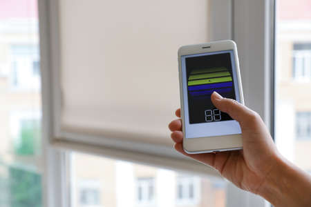 Woman using smart home application on phone to control window blinds indoors, closeup. Space for text Stock Photo