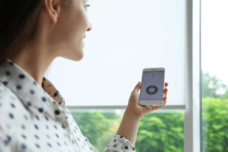 Woman using smart home application on phone to control window blinds indoors Banque d'images